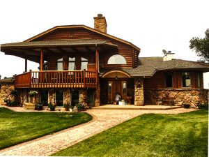 Log sided home with stone on lower. Green grass.